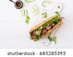 Small photo of Sandwich of whole wheat bread with roast beef, cucumber and arugula. Top view. Flat lay.