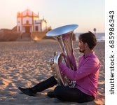 Small photo of Young musician playing the trumpet on the sea coast. Tuba instrument. In the background is the Chapel Senhor da Pedra at Miramar Beach, Atlantic ocean, Porto, Portugal.