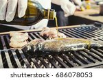 Small photo of Grilled fish with spices covering with olive oil on fire