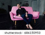man model sits on pink sofa in... | Shutterstock . vector #686150953
