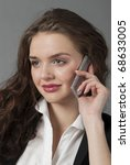 The young beautiful girl in a white blouse and a black jacket speaks by phone - stock photo