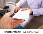 Small photo of Close-up Of A Businessman Giving Cheque To Her Colleague At Workplace In Office