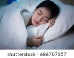 asian woman sleeping in a bed... | Shutterstock . vector #686707357