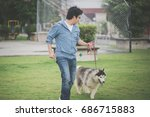 Stock photo asian man walking with a siberian husky don in the park 686715883