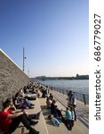 Small photo of Cologne/Germany - May 10, 2017: Locals and tourists alike are enjoying the early evening sunshine on the banks of the Rhine river at the base of the Hohenzollern Bridge
