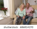 couple sitting on a sofa using... | Shutterstock . vector #686814193