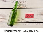 Small photo of Lying bottle, red paper message. Stop drink and make your life better.