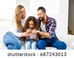 young parents sitting on the... | Shutterstock . vector #687243013