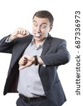 Small photo of Businessman is late. Brushes his teeth and looks at his watch in panic.