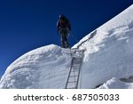 Small photo of A mountaineer using steel ladder to cross an abysmal crevasse in the Himalayan region.