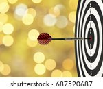 Small photo of close up dart arrow hitting on target center on bullseye in dartboard with blurred golden bokeh background, perfection goal success, symbol of aim and achievement