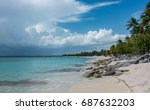 Small photo of Storm clouds approach the desolate island of Catalina (Isla Catalina), in the Dominican Republic, with beautiful palm tree lined sandy beach with rock formations.