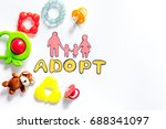 Small photo of Adopt word, paper silhouette of family and toys on white background top view copyspace