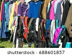 Small photo of many belts and adult clothing on rack display at garage sale or thrift store to resale, reuse, recycle, exchange or donate outdoor