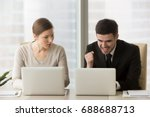 Small photo of Resentful employee loser looks enviously at promoted colleague winner enjoying success, good news while working on laptop, feels jealous about rivals achievements, team rivalry, unfair competition