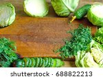 Small photo of Frame of green groceries, cabbage, cucumber and herbs on natural wooden background