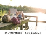 girl reading a book outside in... | Shutterstock . vector #689113327