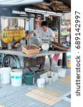 Small photo of GEORGE TOWN, PENANG, MALAYSIA - JUL 26, 2017: A street hawker at his roasted chestnut stall in Chowrasta market in Jalan Chowrasta. Penang traditional lifestyle is part of the UNESCO world heritage.