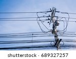 Small photo of Utility Pole against Blue Sky supporting overhead power lines, electrical cable, fibre optic cable, transformers and street lights.