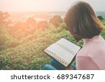 woman reading bible on mountain ... | Shutterstock . vector #689347687