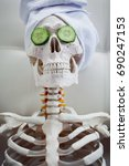 Small photo of Skeleton in Spa salon with towel on her head and mask on her face, relaxes. An absurd concept, social parody. Take care of beauty and forget about inner peace
