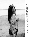 Small photo of Pretty brunette woman in pin up style have fun and enjoying life on vacation. Stylish inspire vintage lady on a beach near wooden alcove, water and sand