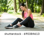 woman knee pain in a park   Shutterstock . vector #690384613