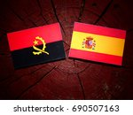 Small photo of Angolan flag with Spanish flag on a tree stump isolated