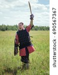 Small photo of A warrior is a nomad in the steppe against the background of the forest and the cloudy sky. Goes into the attack, raising his sword high, shouting a battle cry.