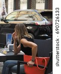 Small photo of TURIN, ITALY - CIRCA JULY 2017: Woman seated at alfresco bar in the city centre