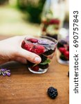 holding a glass with infused... | Shutterstock . vector #690757843