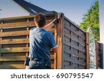 Small photo of Man with artificial heart strokes a wood fence in the garden.