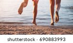 young couple running into water ... | Shutterstock . vector #690883993