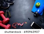 Small photo of Health fitness background. Sneakers, dumbbell, power grip, green apple. water bottle, blue towel, phone and earphone on dark background.