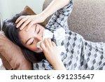 sick woman blowing her nose...   Shutterstock . vector #691235647
