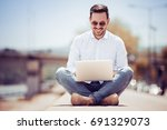 handsome young man using laptop ... | Shutterstock . vector #691329073