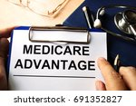 Small photo of Medicare advantage in a clipboard. Health care insurance concept.