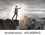 Small photo of Blindfold businessman standing on tip of cliff