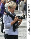 Small photo of Prague, Czech Republic - September 16, 2010: European elderly lady amateur photographer with two cameras