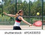 woman playing padel outdoor | Shutterstock . vector #691433053