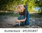 mother hugging her son outdoor | Shutterstock . vector #691501837
