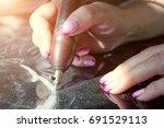 girl engraves on granite | Shutterstock . vector #691529113