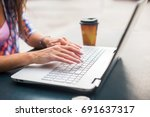 young woman typing on a laptop... | Shutterstock . vector #691637317