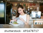asia woman taking photo food on ... | Shutterstock . vector #691678717