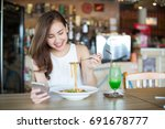 young asia woman eating food at ... | Shutterstock . vector #691678777