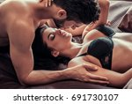 Stock photo young couple is having sex lying on bed at home man tenderly kissing his woman 691730107