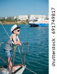 Small photo of cool cute little boy captain wearing sunglasses aboard luxury boat in sunny summer day