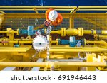 Small photo of Instrumentation operation technician calibrating oil field instrument, Coriolis flow meter and actuated control valve on offshore oil and gas platform.