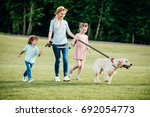 Stock photo happy young mother with adorable kids and dog walking in park 692054773