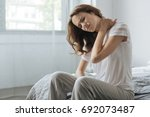 moody young woman holding her... | Shutterstock . vector #692073487